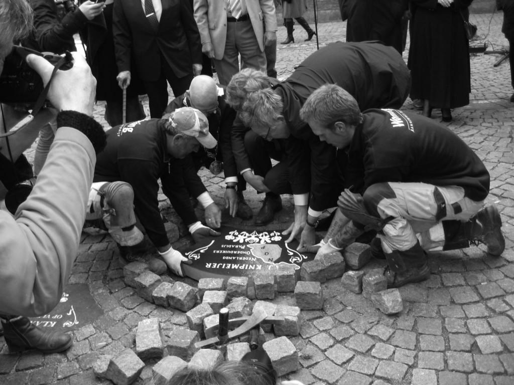 Steenlegging op het Koeplein onder de Nieuwe Toren in Kampen op 30 april 2015. De burgemeesters van Kampen en de Noordoostpolder vlijen de gedenksteen met hulp van stratenmakers.